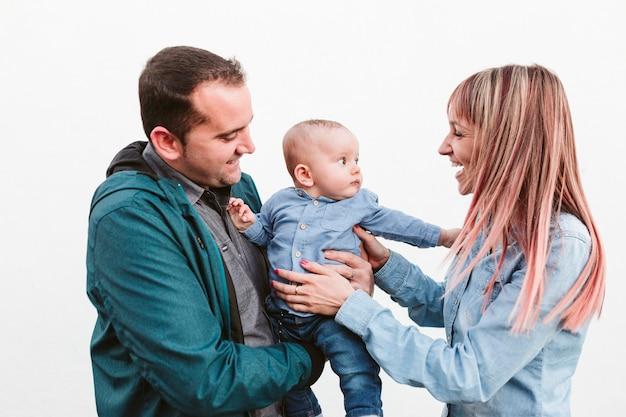 Szczęśliwa rodzina na zewnątrz o zachodzie słońca, ojciec, matka i syn gra. koncepcja rodziny
