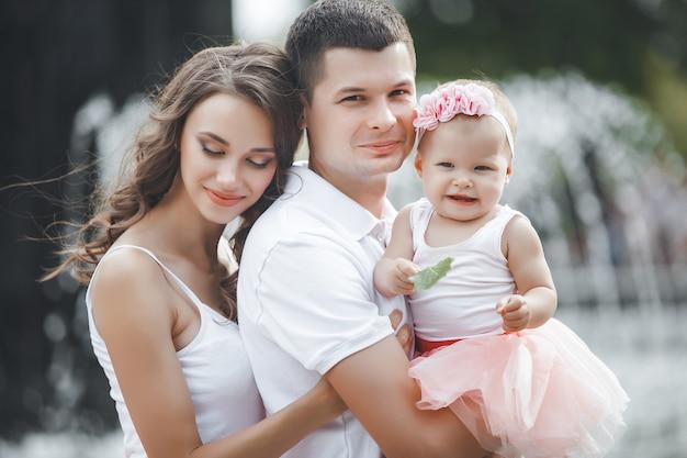 Szczęśliwa rodzina na zewnątrz. rodzice chodzą po parku ze swoim małym słodkim dzieckiem. młoda rodzina