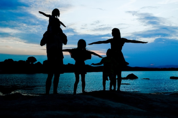 Szczęśliwa rodzina nad morzem na sylwetka przyrody