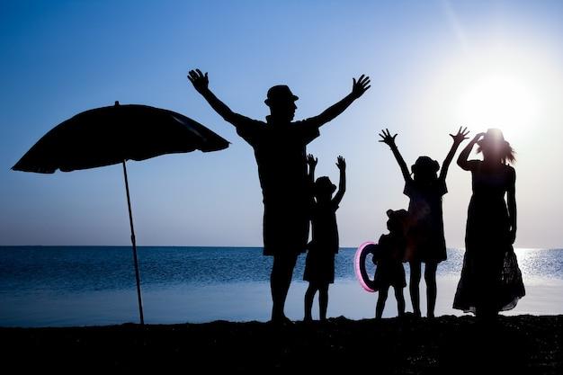 Szczęśliwa rodzina nad morzem o zachodzie słońca w podróży sylwetka w przyrodzie
