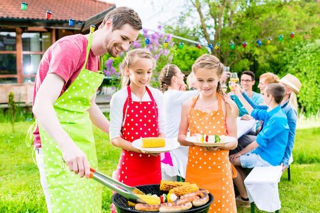 Szczęśliwa rodzina o grillu na przyjęciu w ogrodzie