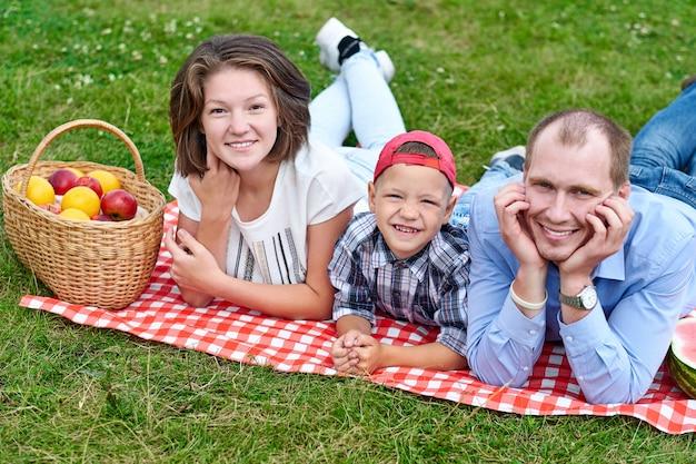 Szczęśliwa rodzina odpoczynku w przyrodzie. matka, ojciec i dziecko cieszą się i leżą na kraciastej kracie na łące