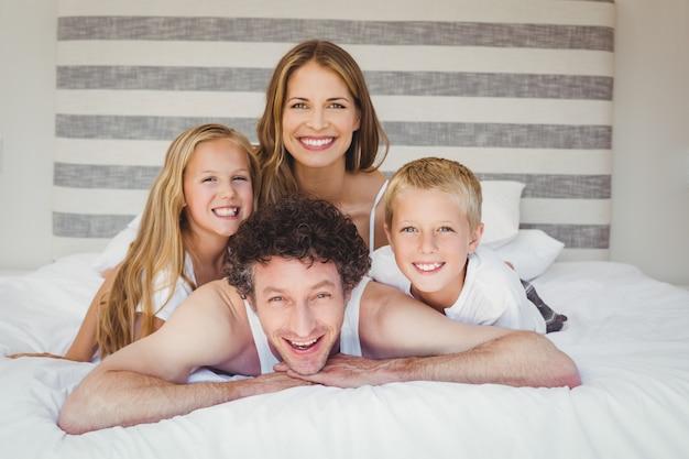 Szczęśliwa rodzina odpoczywa na łóżku