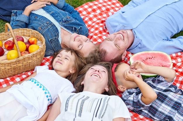 Szczęśliwa rodzina odpoczywa na pikniku. ciesząc się i leżąc na kratkę na łące. dorośli i dzieci patrzą w niebo.