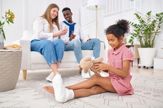Szczęśliwa rodzina odpoczywa w salonie. matka, ojciec i córka pozują razem w domu, dobry związek. mama, tata i córeczka, sesja zdjęciowa w domu