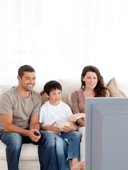 Szczęśliwa rodzina ogląda telewizję podczas gdy jedzący popkorn wpólnie