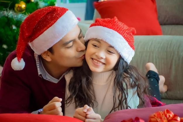 Szczęśliwa rodzina. ojca buziaka córka w żywym pokoju w domu w bożenarodzeniowym wakacje.