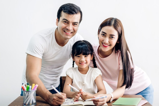 Szczęśliwa rodzina ojciec i matka z córką, uczenie się i pisanie w zeszycie z ołówkiem, odrabianie lekcji w domu. koncepcja edukacji