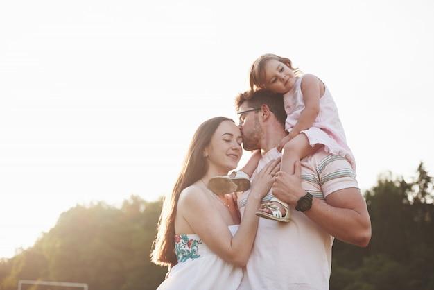 Szczęśliwa rodzina, ojciec matki i córka dziecka w naturze o zachodzie słońca.