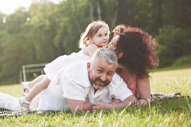 Szczęśliwa rodzina, ojciec matki i córka dziecka w naturze o zachodzie słońca