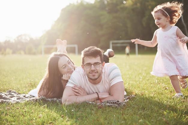 Szczęśliwa rodzina, ojciec matki i córki dziecka w naturze o zachodzie słońca