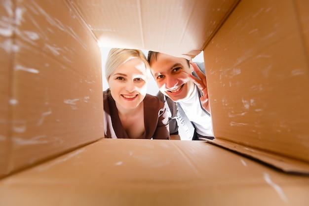 Szczęśliwa rodzina otwierając kartonowe pudełko - ruchoma koncepcja
