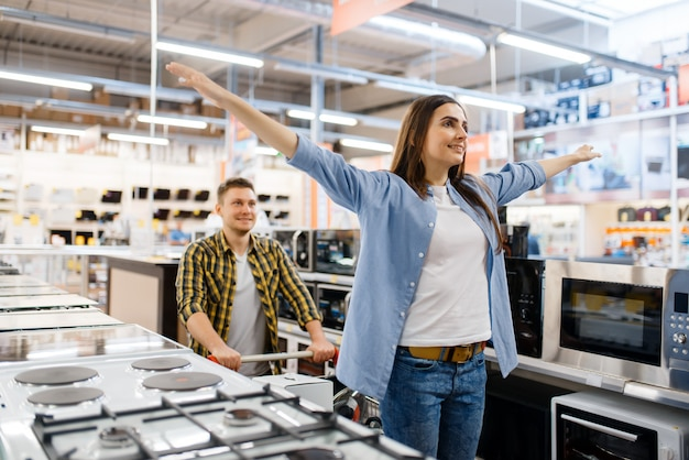 Szczęśliwa rodzina para z wózkiem w sklepie elektronicznym. mężczyzna i kobieta kupują domowe urządzenia elektryczne na rynku