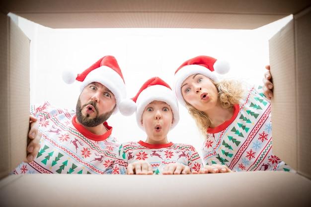 Szczęśliwa rodzina patrząc do pudełka. zaskoczeni ludzie rozpakowują świąteczne pudełko. boże narodzenie koncepcja wakacje. niski kąt widzenia.