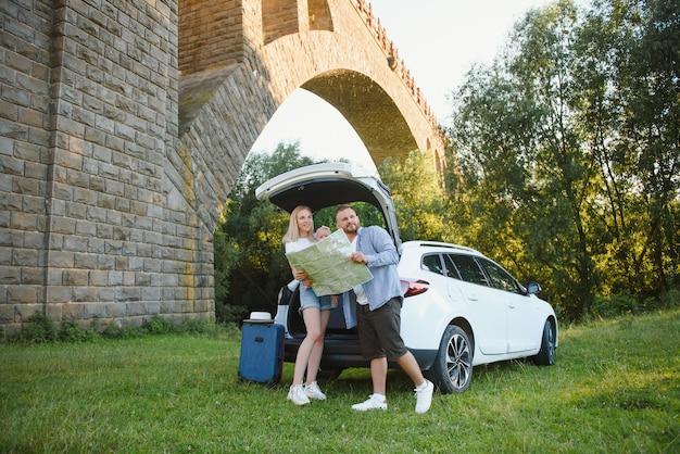 Szczęśliwa rodzina patrząca na mapę obok samochodu