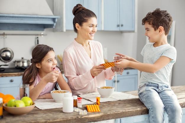 Szczęśliwa rodzina. piękna, zadowolona ciemnowłosa młoda matka uśmiecha się i podaje tabletki swojemu synowi siedzącemu na stole i córce jedzącej śniadanie