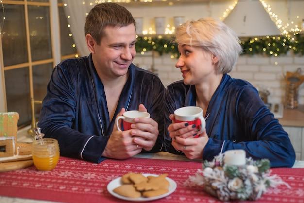 Szczęśliwa rodzina pijąca gorącą herbatę w kuchni w świąteczny obiad rodzinny