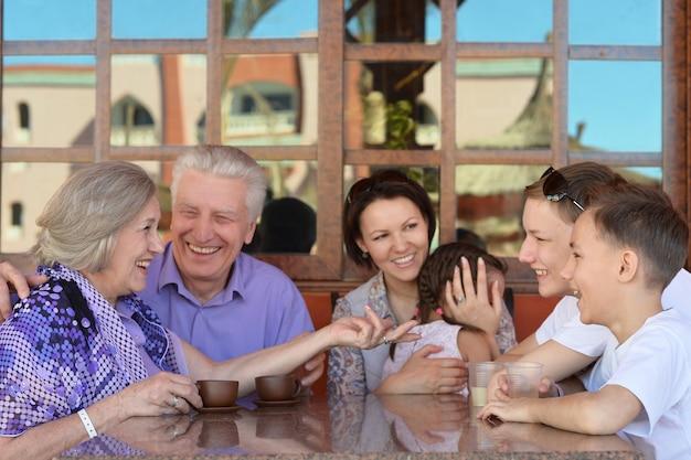 Szczęśliwa rodzina pijąca herbatę przy stole na zewnątrz w okresie letnim