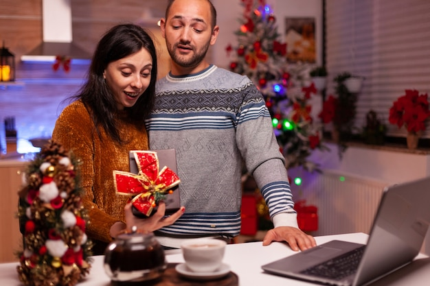 Szczęśliwa rodzina pokazuje prezent ze wstążką na nim podczas wideorozmowy online