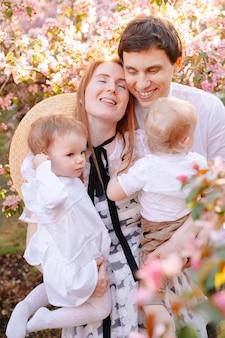 Szczęśliwa rodzina portret rodziców z dziećmi kwitnącej różowej jabłoni w parku uśmiechnięta mama i tata przytulają swoje dzieci na spacerze po parku
