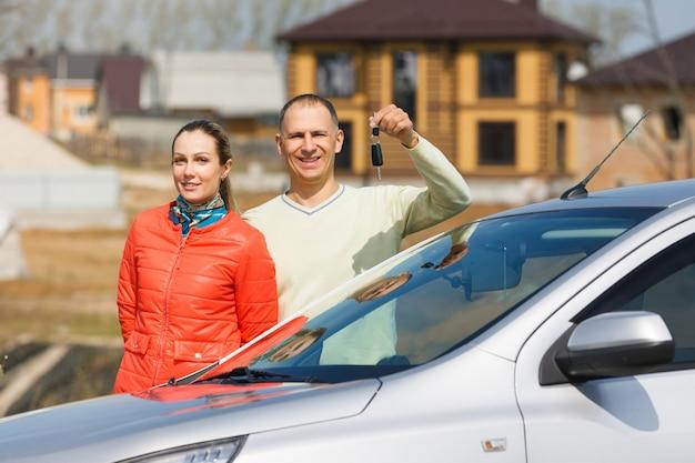 Szczęśliwa rodzina posiada klucze do samochodu na tle domu