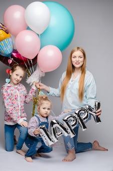 Szczęśliwa rodzina pozuje podczas gdy świętujący przyjęcie urodzinowe