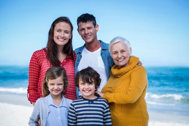 Szczęśliwa rodzina pozuje przy plażą