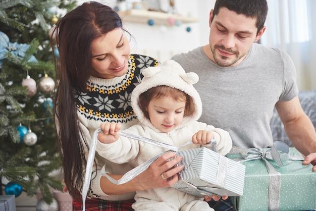 Szczęśliwa rodzina przy bożymi narodzeniami w ranku otwiera prezenty wpólnie blisko jedlinowego drzewa. pojęcie szczęścia i dobrego samopoczucia rodziny