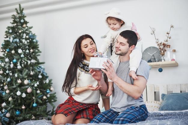 Szczęśliwa rodzina przy bożymi narodzeniami w ranku otwiera prezenty wpólnie blisko jedlinowego drzewa.