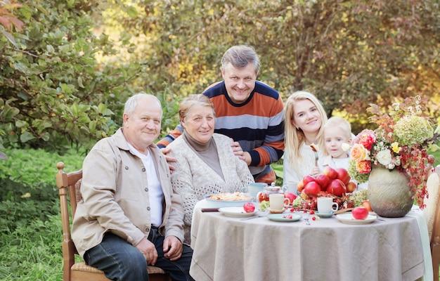 Szczęśliwa rodzina przy nakrytym stole z szarlotką w ogrodzie