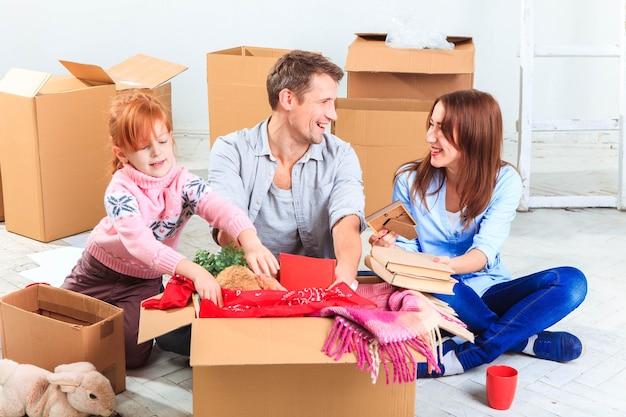 Szczęśliwa rodzina przy naprawie i przeprowadzce. rodzina siedzi i wyciąga rzeczy z pudeł na tle nowego białego mieszkania