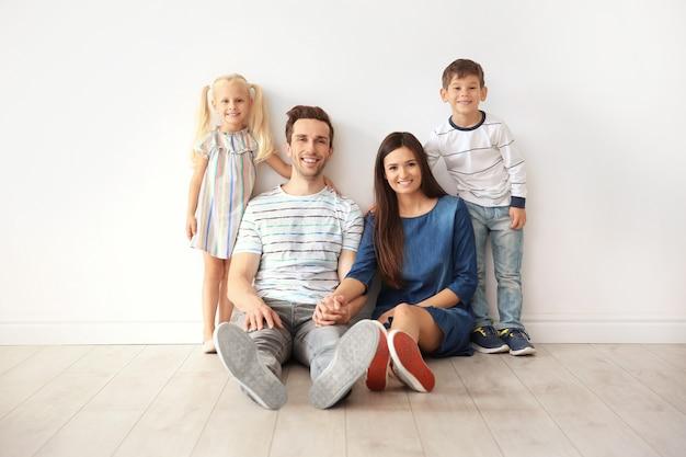Szczęśliwa rodzina przy ścianie w swoim nowym domu
