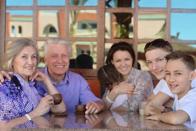 Szczęśliwa rodzina przy stole na świeżym powietrzu w okresie letnim