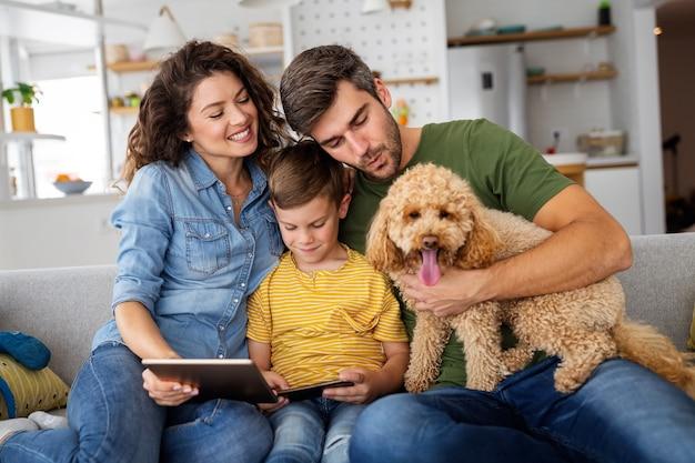 Szczęśliwa rodzina przy użyciu urządzeń technologicznych razem w domu. ludzie, koncepcja edukacji.