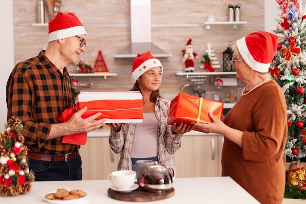 Szczęśliwa rodzina przynosząca świąteczny prezent ze wstążką świętującą święta bożego narodzenia