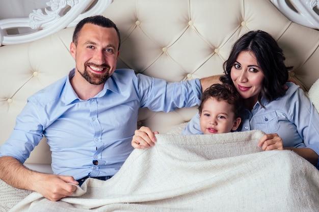 Szczęśliwa rodzina przystojny mężczyzna i urocza kobieta i ich dziecko (mały synek) odpoczywają i bawią się w chowanego razem na łóżku w sypialni