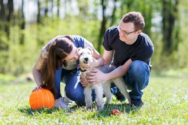 Szczęśliwa rodzina przytulanie psa w parku lato