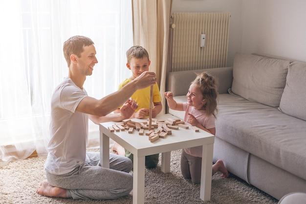 Szczęśliwa rodzina razem grając w grę planszową. dom. przytulny.