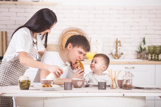 Szczęśliwa rodzina razem jedząc śniadanie. młody rodzinny łasowanie przy stołem na kuchni. mama, tata i małe dziecko jedzą.