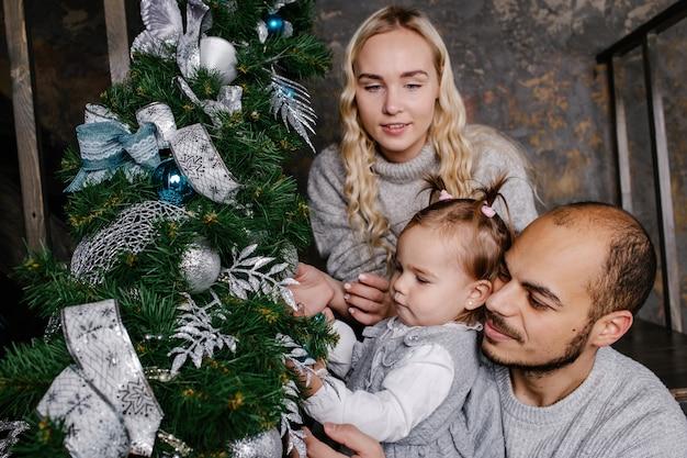 Szczęśliwa rodzina razem udekoruj choinkę świąteczną w domu.