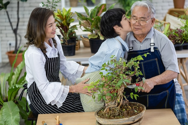 Szczęśliwa rodzina razem w ogrodzie, dziadek wnuk i kobieta dbająca o przyrodę