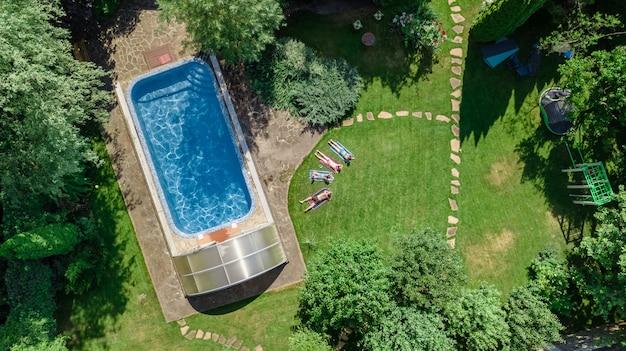 Szczęśliwa rodzina relaksując się przy basenie, widok z lotu ptaka z drona rodziców i dzieci baw się na wakacjach, rodzinny weekend w ośrodku