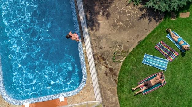 Szczęśliwa rodzina relaksując się przy basenie, widok z lotu ptaka z góry rodziców i dzieci baw się na wakacjach, rodzinny weekend na miejscu