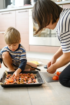 Szczęśliwa rodzina robi jedzeniu w domu. mama razem jej czteroletni maluch syn syna gotowania pizzy w kuchni.