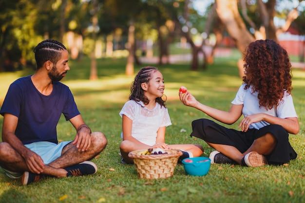 Szczęśliwa rodzina robi piknik w parku