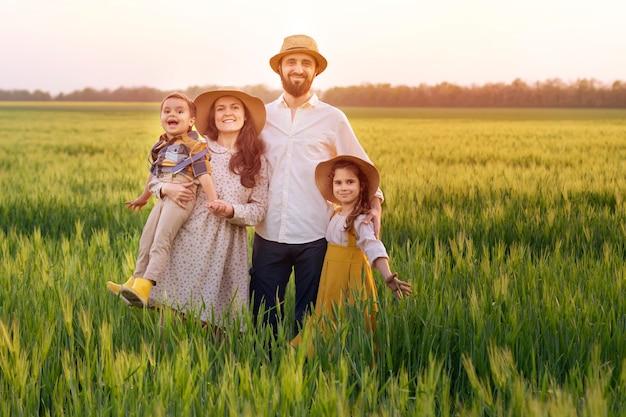 Szczęśliwa rodzina rolników, ojca, matki, syna i dziewczyny w słomkowym kapeluszu na polu pszenicy o zachodzie słońca.