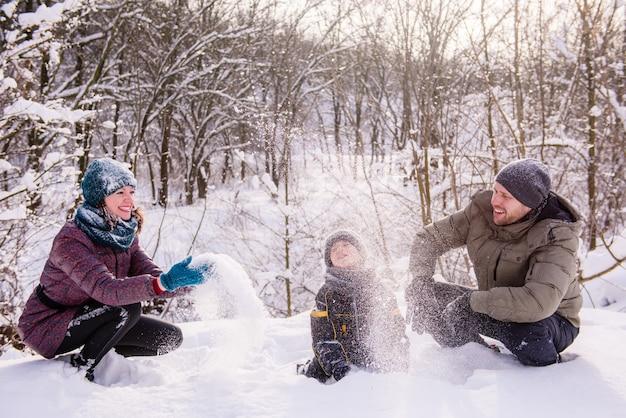 Szczęśliwa rodzina rzucać śniegiem w zimowym lesie