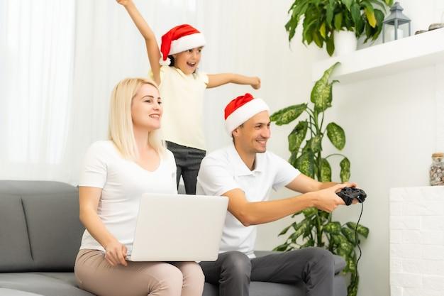 Szczęśliwa rodzina siedzi na kanapie i gra w gry wideo. boże narodzenie