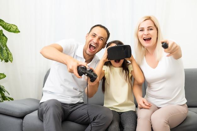 Szczęśliwa rodzina siedzi na kanapie i gra w gry wideo.