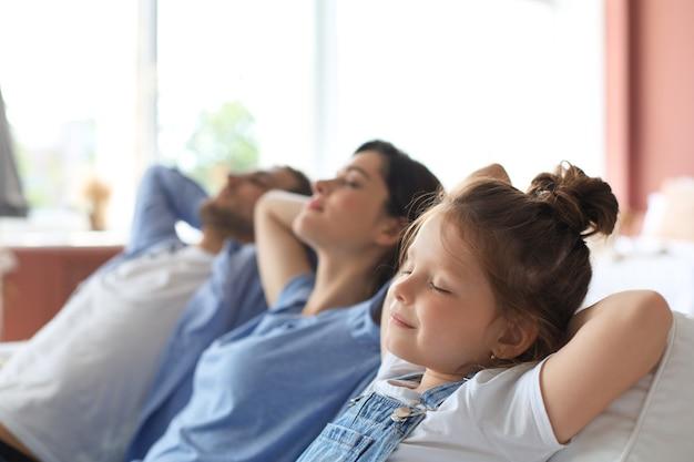 Szczęśliwa rodzina siedzi na kanapie w domu.